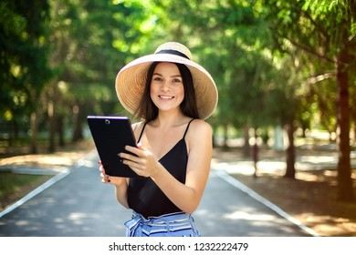 happy girl with a tablet in hand and wearing a hat, business and social activity on the Internet being in nature