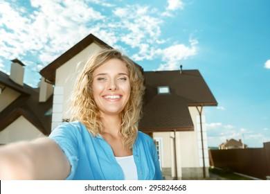 Happy girl taking selfie of her new house