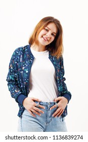 Happy girl teenager in bomber and jeans poses in white studio