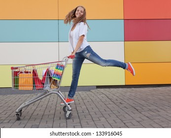 The happy girl the teenager joyfully jumps near to the cart full of purchases