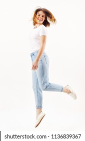 Happy girl teenager in t-shirt and jeans jumps in white studio, full body