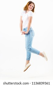 Happy girl teenager in white t-shirt and jeans jumps in white studio, full body