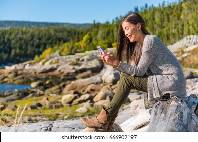 Happy girl texting sms message on mobile phone on nature forest hike in autumn outdoors. Asian woman playing on cellphone