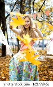 Happy girl throws colorful autumn leaves
