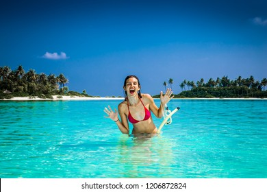 Happy girl at topical beach on Olhuveli island in Maldives.
