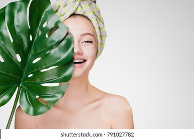 happy girl with a towel on her head holds in her hand a big leaf