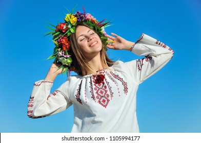 Happy girl in traditional Ukrainian shirt with a wreath on blue sky background