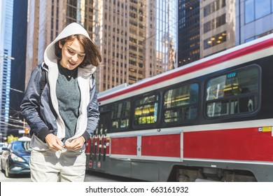 Happy girl travelling in the city. Portrait of a young woman with short hair, wearing a hoodie and jacket, walking next to a busy road with skyscrapers on background. Travel and lifestyle concepts.