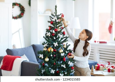 Happy girl trying to put red decorative star on top of Christmas tree while decorating it