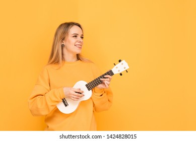 Happy girl with ukulele in her hands stands on an orange background, looks sideways and smiles, wears yellow casual clothing. Smiling girl musician plays ukulele. Isolated.