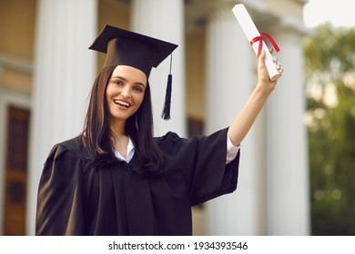 Happy girl university graduate in traditional costume standing and holding diploma in raised hand expressing happy celebration over university building background. Graduation from university concept