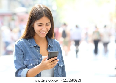 Happy girl uses a smart phone walking in the street of a big city