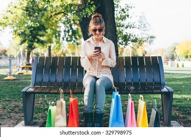 Happy girl using smart phone after holiday shopping