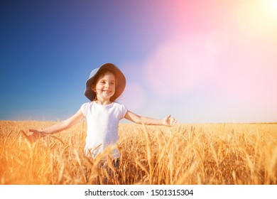 Happy girl walking in golden wheat, enjoying the life in the field. Nature beauty, blue sky and field of wheat. Family outdoor lifestyle. Freedom concept. Cute little girl in autumn field