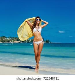 Happy girl walking on the beach enjoying summertime