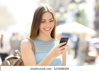 Happy girl walking in the street checking smart phone content