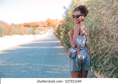 Happy girl walking in a street in the middle of the nature with a backpack on her shoulder