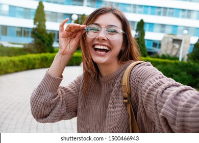 Happy girl walks down the street in spring around the city.Closeup selfie-portrait student of attractive girl in sunglasses with long hairstyle and snow-white smile in city.