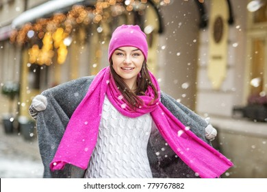 A happy girl walks in hats, scarves and mittens. Snow. Copy Space Concept Lifestyle, Urban, Winter, Vacation, Happy Christmas, New Year.