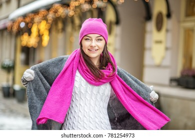 A happy girl walks in hats, scarves and mittens. Copy Space. Concept Lifestyle, Urban, Winter, Vacation, Happy Christmas, New Year.