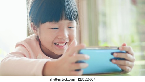 happy girl watch video or play mobile game by smart phone