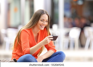Happy girl watching media content in a smart phone sitting on a bench in the street
