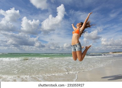 Happy girl wearing bikini jumping on the beach on holidays with a cloudy sky in the background