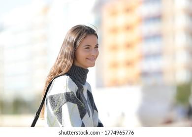 Chica feliz con camiseta mirando lejos en la calle en invierno un día soleado