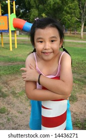 Happy girl wearing pink singlet at the playground