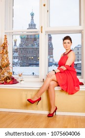 happy girl wearing red dress and red shoes sits on window sill