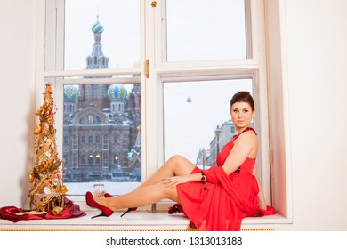 happy girl wearing red dress and red shoes rests on window sill (in window can see Church of the Savior on Spilled Blood)