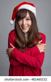 Happy girl wearing santa hat, feeling cold and hug herself,   Christmas concepts, Christmas santa hat concepts.