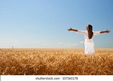 Happy girl in white dress on wheat field