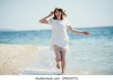 happy girl in white dress  running on the sea beach