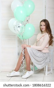 happy girl in white outfit holding mint balloons on studio