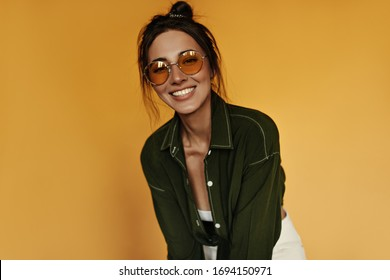 Happy girl in white pants, cropped top and dark green shirt smiles sincerely. Pretty woman in orange sunglasses poses on isolated yellow background.