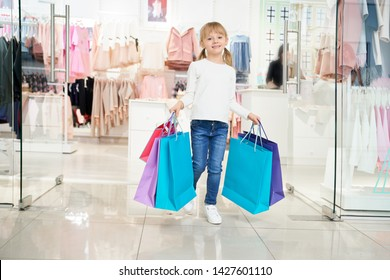 Happy girl in white shirt and jeans keeping paper bags and looking at camera while shopping in mall. Cheerful child looking at camera, smiling and purchasing new clothes. Concept of buying.