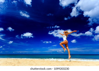 Happy girl in white swimsuit jumping at Karon beach, Phuket, Thailand