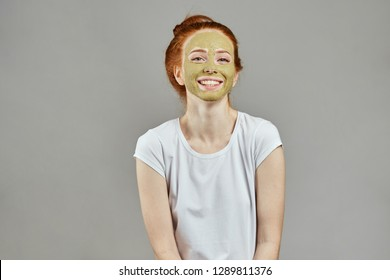 happy girl in white T-shirt with green face looking at the camera. close up photo. happiness, emotion .studio shot