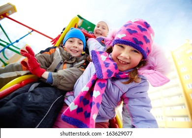 Happy girl in winterwear playing outside with her friends on background