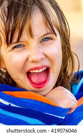 A happy girl wrapped in a beach towel looks at the camera with open mouth and bright eyed excitement.