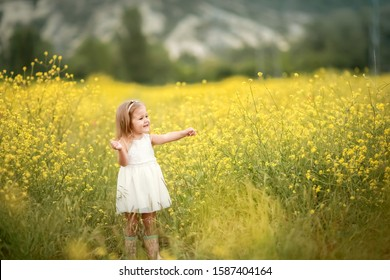 happy girl in a yellow dress staying in the field of flowering rape. Nature blooms rape seed field.