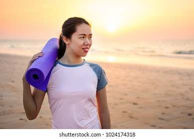 Happy girl with yoga mat on the beach for outdoors workout