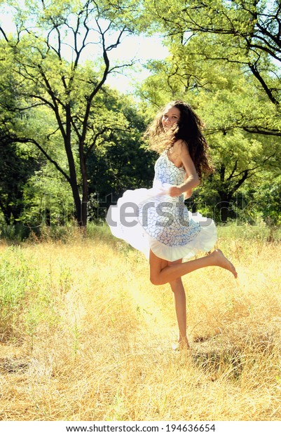 Happy girl. Young woman dancing on the meadow
