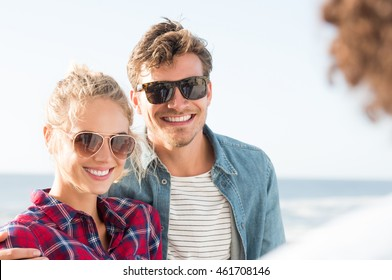 Happy girlfriend and boyfriend having fun and wearing sunglasses during sunset. Portrait of happy couple posing for a picture. Smiling young couple enjoying with their friend.