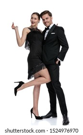 Happy girlfriend posing with her leg in the air beside her boyfriend dressed in a tuxedo and holding his hand in his pocket, standing on white studio background