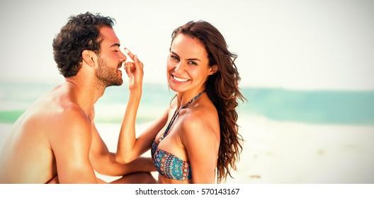 Happy girlfriend putting sunscreen on boyfriends nose at beach