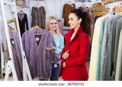 Happy girlfriends choosing warm jacket in store and smiling