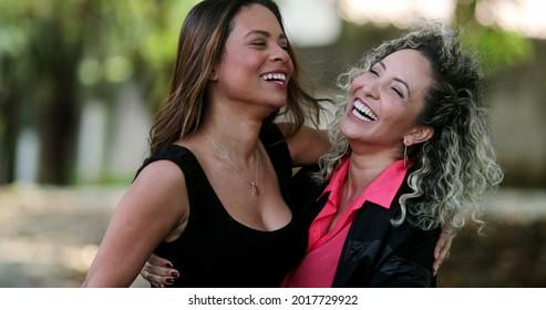 Happy girlfriends joy and embrace, two friends hug feeling happy