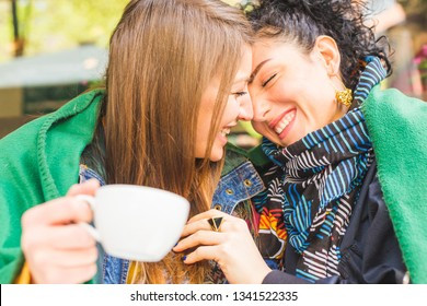 Happy girlfriends in love sharing coffee time together - Playful women friendship concept with girls couple having fun and smiling - Millennials lesbian couple